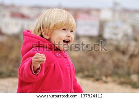 laughing toddler girl running on the walk - stock photo