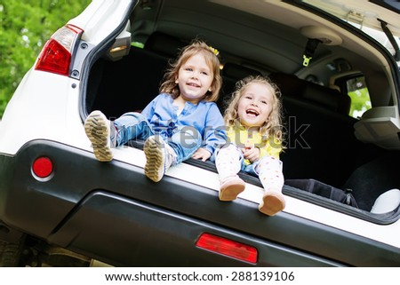 laughing toddler girls sitting in the car in the forest - stock photo