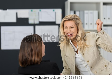 Laughing vivacious attractive middle-aged businesswoman rejoicing with a colleague in the office at their success in a business enterprise - stock photo