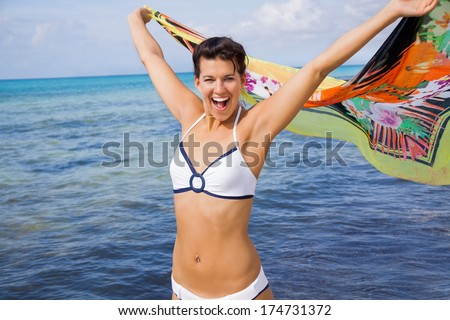Laughing vivacious woman in a bikini at the seaside holding a colourful patterned scarf in her outstretched hands to flutter in the breeze against an ocean backdrop - stock photo