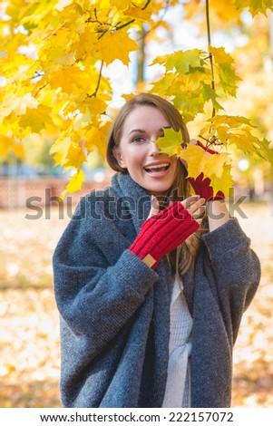 Laughing vivacious woman wearing bright red mittens playing amongst the colorful yellow leaves in an autumn park