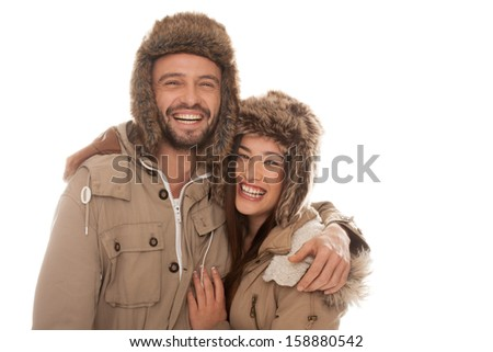 Laughing vivacious young couple in winter fashion standing side by side with their arms around each other in furry hats and warm jackets isolated on white