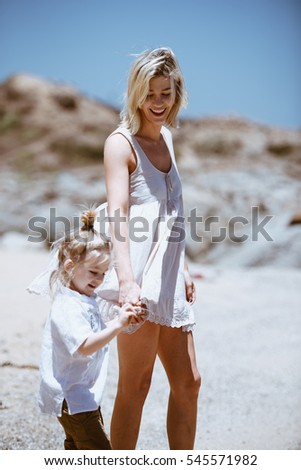 Laughing woman and her child walking on beach. Vertical outdoors shot.