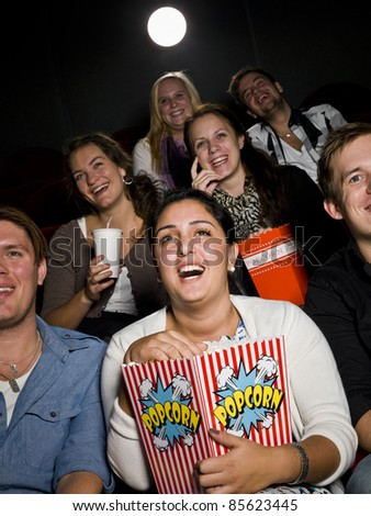 Laughing woman at the cinema with large bag of popcorn - stock photo