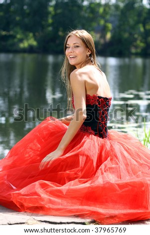 Laughing woman in a red dress sitting near river - stock photo