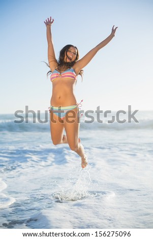 Laughing woman in bikini jumping in the sea on a sunny day - stock photo