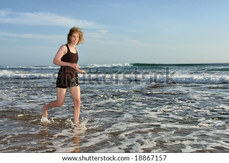 Laughing woman jogs in sea water on beach. Shot in Sodwana Bay Nature Reserve, KwaZulu-Natal province, Southern Mozambique area, South Africa. - stock photo