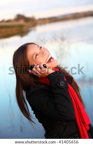Laughing woman on the phone. Casual and natural outside by the water. - stock photo