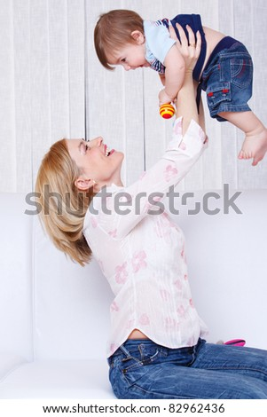 Laughing woman playing with her baby son - stock photo