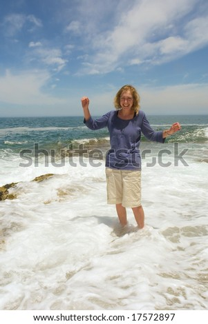 Laughing woman stands in sea-wave foam. - stock photo