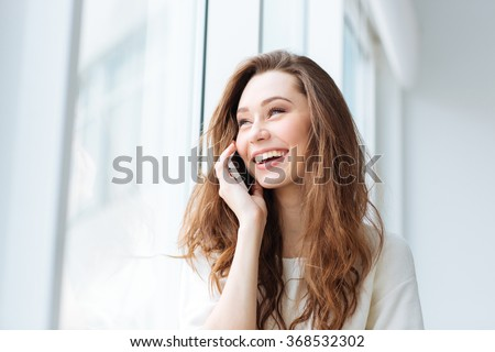 Laughing woman talking on the phone and looking at window - stock photo