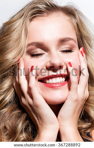 Laughing woman with a sweet smile and red nail polish - stock photo