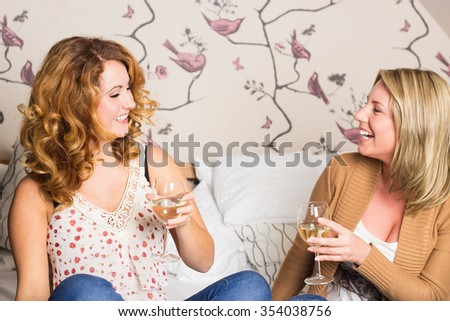 laughing women clinking glasses - stock photo