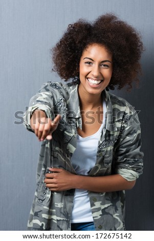 Laughing young African American woman with an afro hairstyle pointing at the camera over a dark grey studio background - stock photo