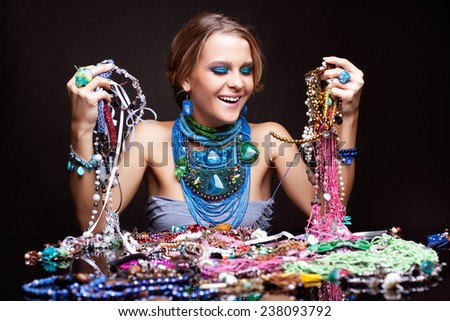 Laughing young beautiful woman over heap of bijouterie on the table with beads in hands - stock photo