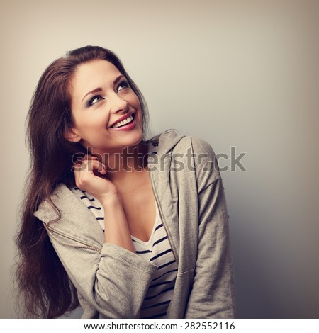 Laughing young casual woman looking up. Closeup vintage portrait with empty copy space - stock photo