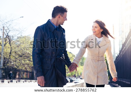 Laughing young couple walking and flirting outdoors - stock photo