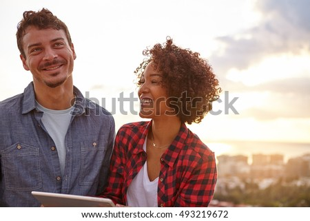 Laughing young couple with a tablet looking dreamily away with the sun setting behind them in spectacular light