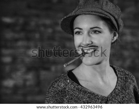 Laughing young gender fluid woman with a cigar in her mouth  - black and white portrait