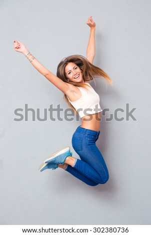 Laughing young girl jumping over gray background. Looking at camera - stock photo