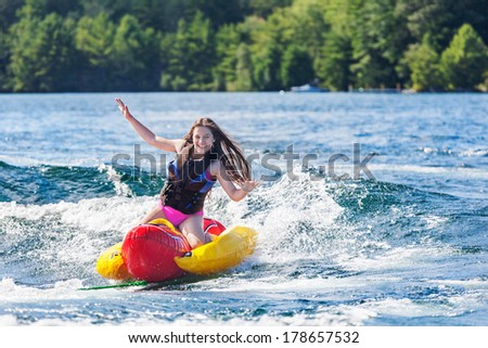 Laughing young girl speeds across a lake, hands in the air, on an inflatable on a summer day - stock photo