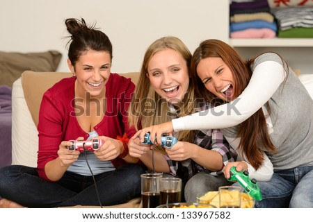 Laughing young girls playing with video games at home - stock photo