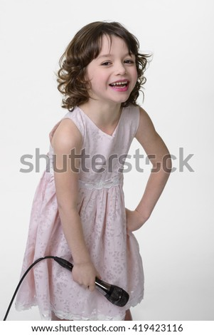 Laughing young princess with microphone in her hands. Close-up vertical shot of caucasian female in plain adorable dress of pastel color. Fantastic emotions of a child with healthy curled hair. - stock photo