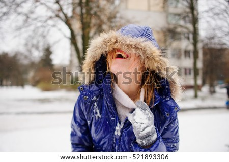 Laughing young woman after fight by snowballs. The woman's face is half hidden by a hood. A coat and gloves in snow, wet hair. The woman shakes out snow from under a collar and laughs from pleasure.
