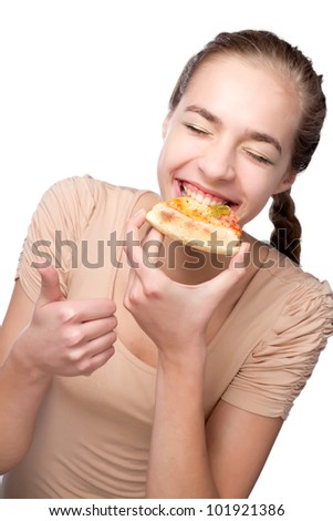 Laughing young woman eating pizza and showing thumb over white background