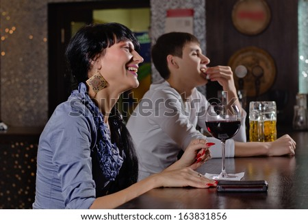Laughing young woman in a pub or nightclub sitting at the bar counter with a large glass of red wine socialising with friends - stock photo
