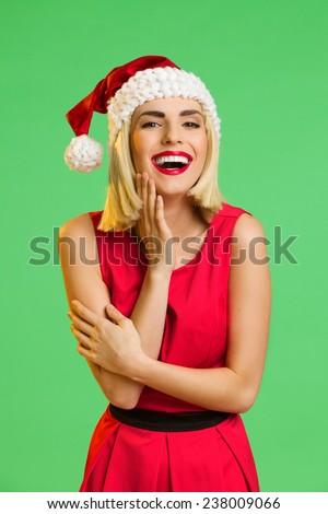 Laughing young woman in santa's hat posing with hand on chin. Waist up studio shot isolated on green. - stock photo