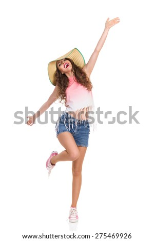 Laughing young woman in straw hat, jeans short, pink top and sneakers standing on one legs with arms outstretched. Full length studio shot isolated on white. - stock photo