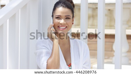 Laughing young woman sitting near fence outdoors