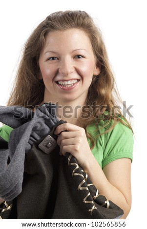 Laughing young woman touches her bag - stock photo