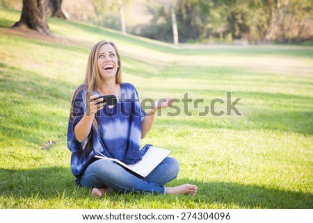 Laughing Young Woman with Book and Cell Phone Outdoors at the Park. - stock photo
