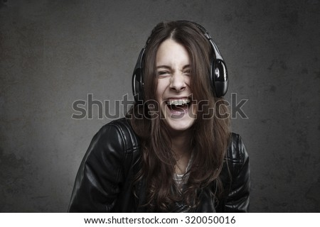 Laughing young Woman with headphones listening music against dark wall background - stock photo