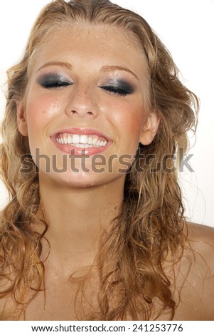 Laughing young woman with wet face and hair.