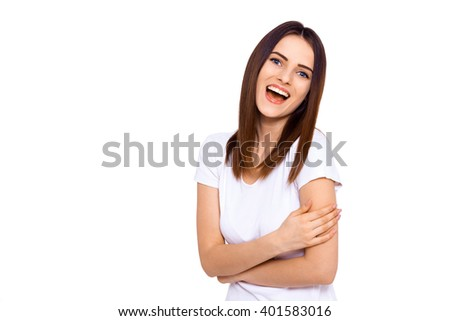 Laughs are fun. Portrait of a beautiful young woman laughing while standing against a white wall - stock photo
