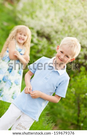 Laughter and smiles of children in a blossoming garden of apple-trees - stock photo