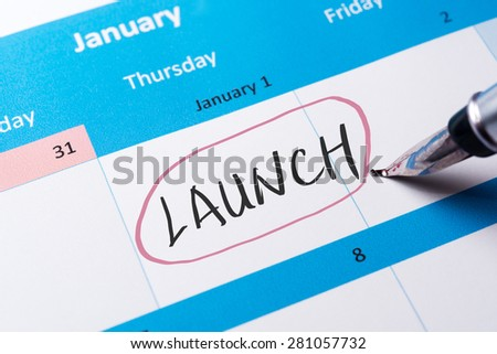 Launch word written on calendar using pen - stock photo