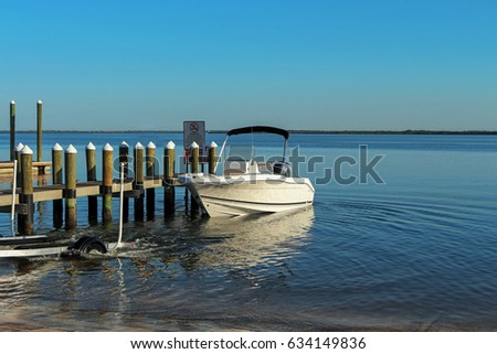 Launching a trailer boat on the boat ramp next to a wooden pier in the Tampa Bay