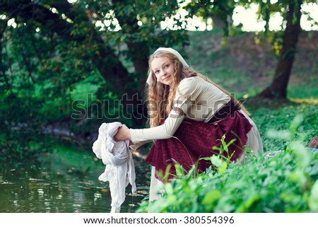 laundress washes the laundry by the river.Woman doing laundry