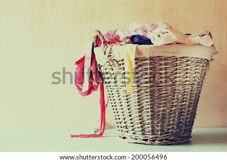 laundry basket full with clothes. vintage toned image. - stock photo