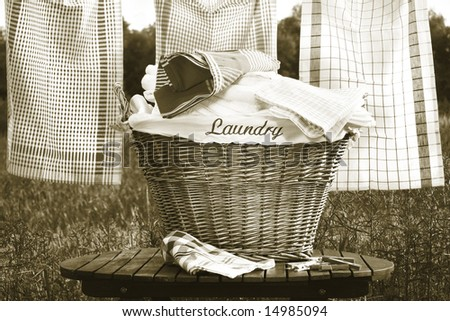 Laundry basket on rustic table with clothesline/ Sepia tone - stock photo