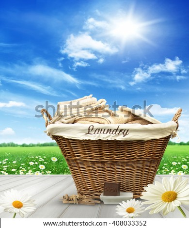 Laundry basket with clothes on rustic table against blue  summer sky