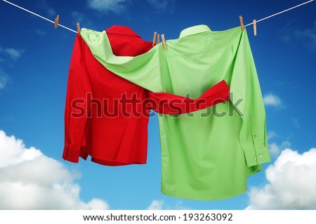 Laundry hanging on a clothesline concept for love and romance with two shirts embracing each other looking at a blue sky - stock photo