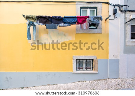 Laundry hanging outside a typical exterior of old houses in narrow street in Bairro Alto in Lisbon, capital of Portugal, leading to a colorful composition - stock photo