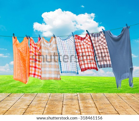 Laundry hanging over flower field with wooden floor - stock photo
