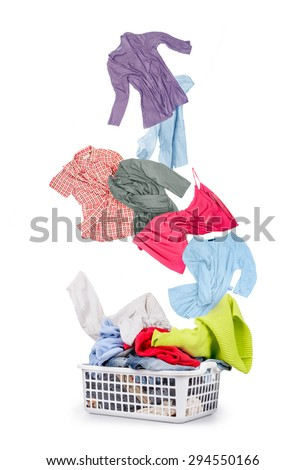 Laundry in a basket and falling clothes - isolated on a white ba - stock photo
