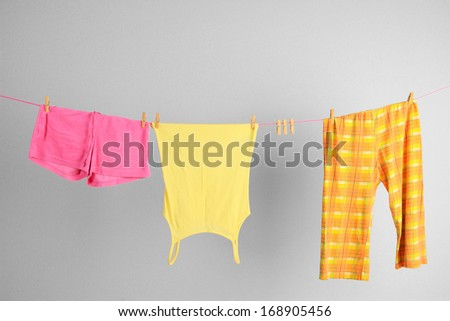 Laundry line with clothes on wall background - stock photo